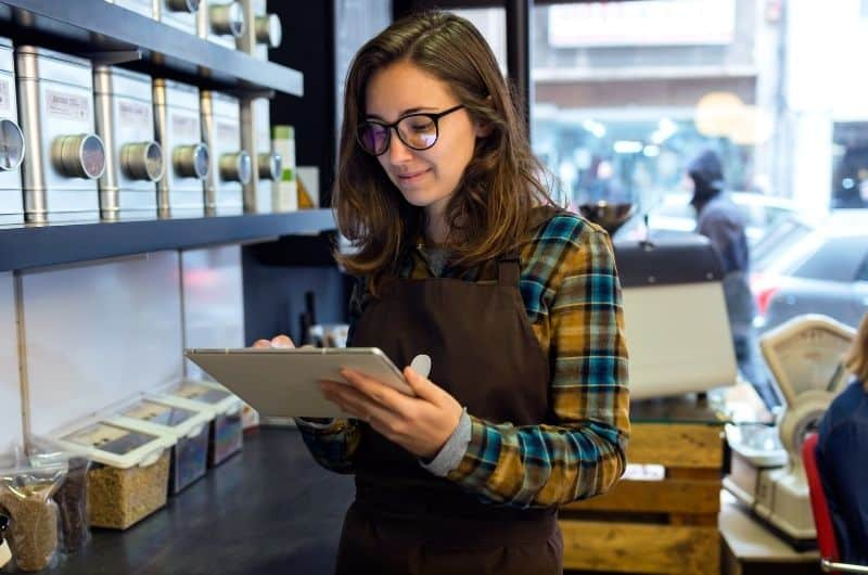 """A female business owner reviewing her business inventory to prepare her """"cost of goods sold"""" for her yearly business taxes"""