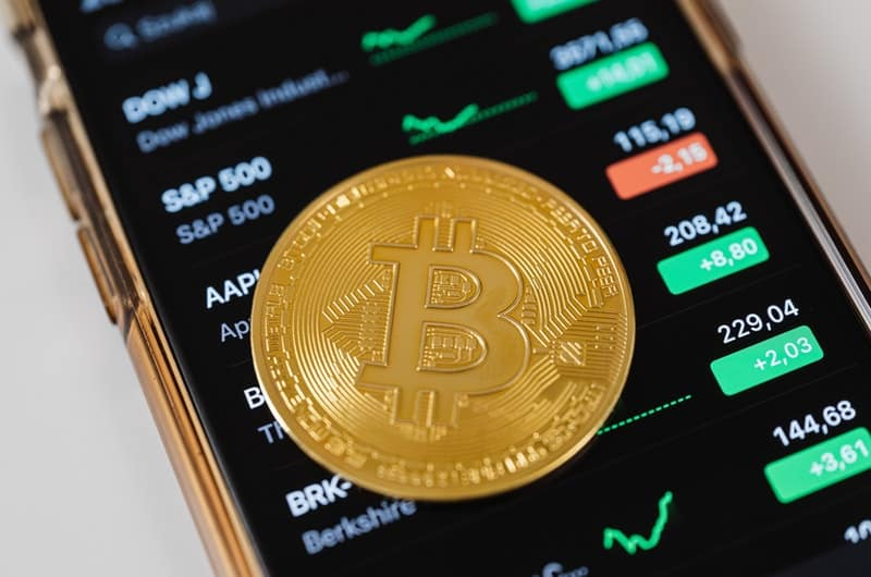 A bitcoin is laying on top of a mobile phone that's showing market trends.