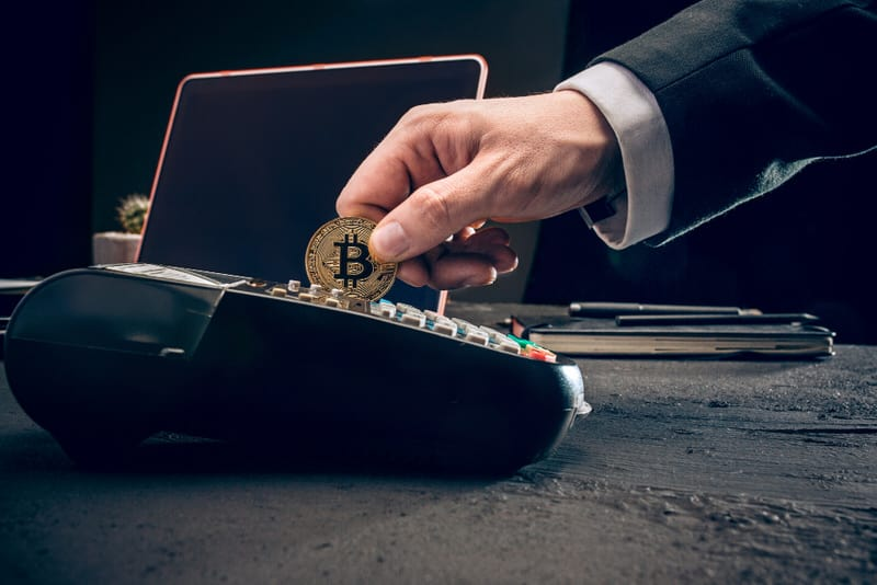 A man trying to swipe a bitcoin like he would a credit card. Bitcoin does not store value like gold, so its value is assumed.