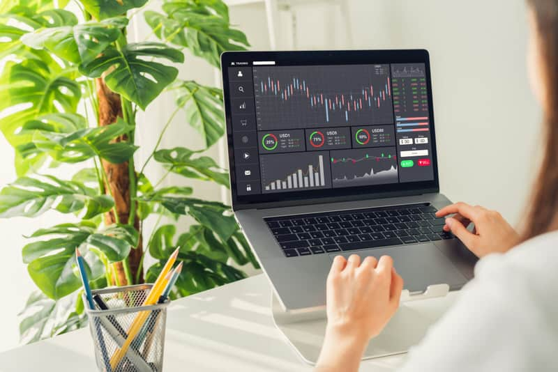A young woman is on her computer trading with both her cash and margin investing accounts.