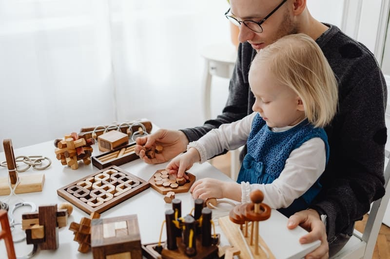 """A young dad is playing with his toddler girl. His """"why"""" to becoming a millionaire is to be financially independent for the safety and comfort of his family."""
