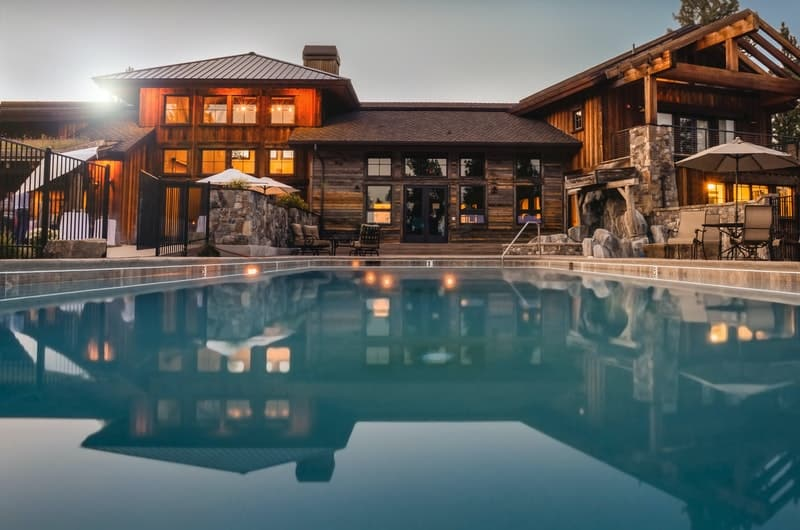 The view of a beautiful million-dollar home and a large pool in the backyard.