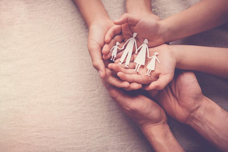 """A family bringing out their hands together to show """"embrace""""."""