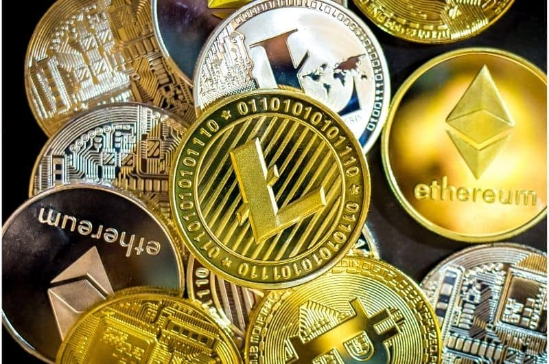 A bunch of ethereum and litecoin coins laid out on a table.
