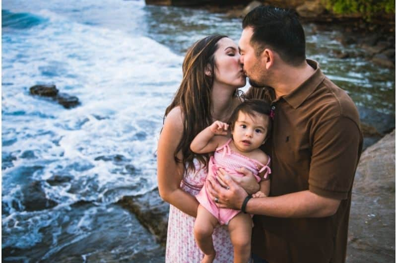 A happily married couple kissing and holding their baby girl. They're happy to be secured and confident in their financial future.