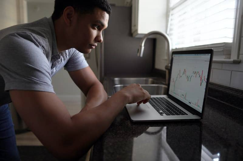 A young man is on his laptop, finding indirect ways to invest in the company Hulu, since it's a private company.