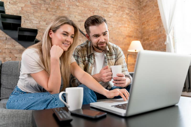 A couple are working together on their laptop, to manage their personal finances like a business.