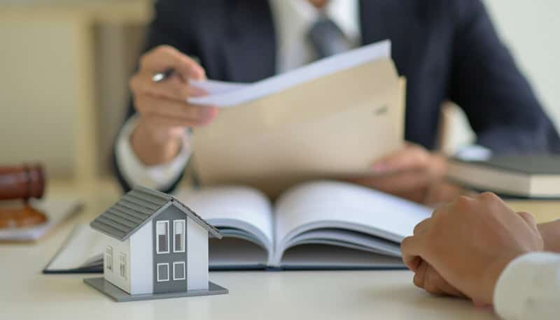 A lawyer is reviewing a million-dollar mortgage contract with his clients.