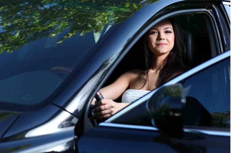 A woman sitting happily in her car. Getting the car insured is a vital expense that will protect you and relieve a big burden in case you get in an accident.