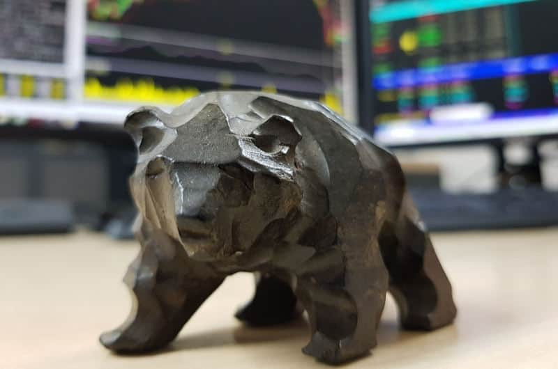 A wood carving of a bear, sitting in front of 2 monitors that are showing stock investing data, representing a bear market.