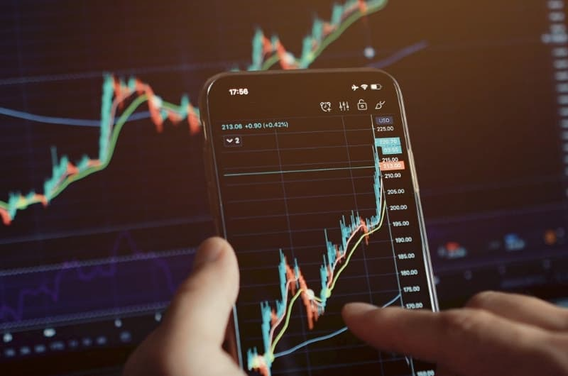 A man is looking at his investments on his computer and phone and is happy to see the great increase in his portfolio value, largely because of the current bull market.