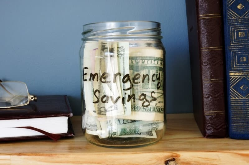 An emergency fund jar on a shelf, with lots of individual US bills inside.