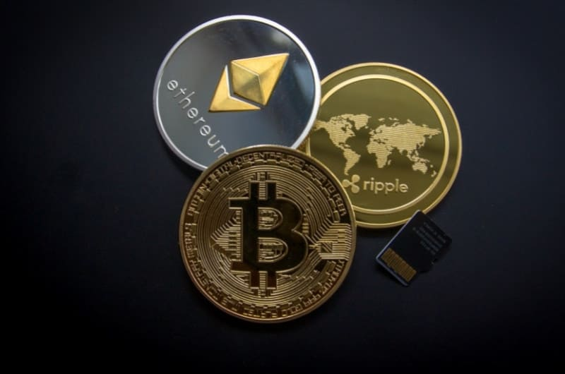 A visual of a physical bitcoin, ripple coin, and ethereum coin.