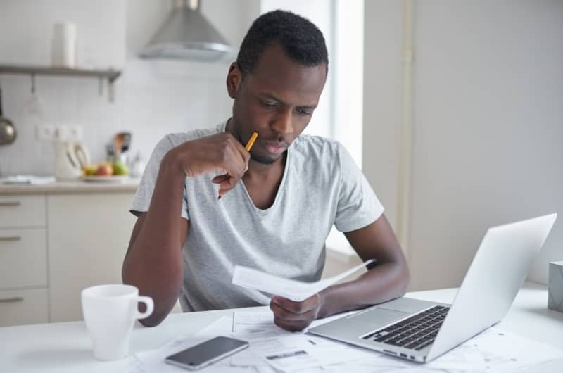 A young man is sitting at his desk reviewing the expensive bill he just received from his financial advisor. He isn't too happy about it.