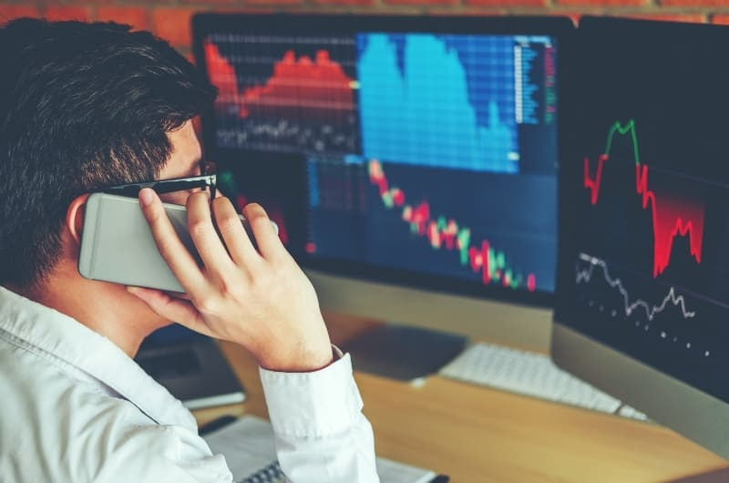 A young investor is on the phone, stressing out after seeing what looks like a stock market correction on his live trading app.