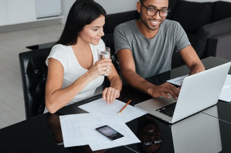 A young couple is reviewing their dollar-cost investing strategy together, and are happy with the upside results so far.