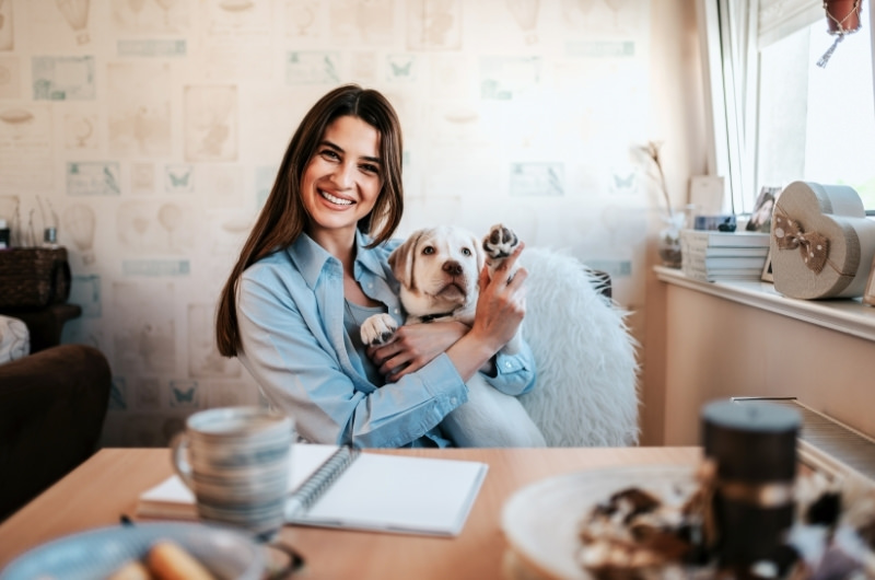 A young woman is happy after moving into a more affordable apartment with her dog.