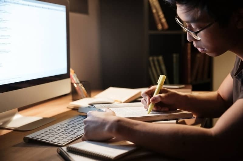 A young man is learning and taking notes from his online course he enrolled in, to increase his skills and future salary.