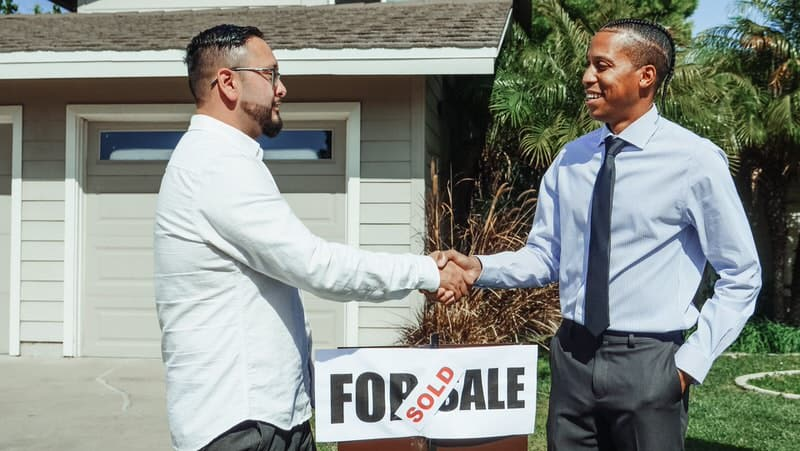 """A realtor has just closed on a home for his recent client, they're shaking hands outside the house """"sold"""" sign."""