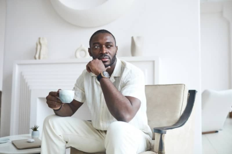 A wealthy self-made entrepreneur is sitting in his luxury home, drinking coffee and thinking of his next business idea.