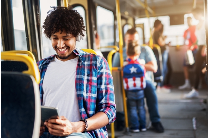 A young man is using public transportation to save money on car expenses.