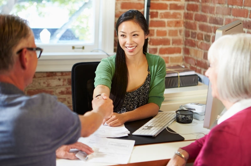 A financial advisor is helping an older couple with their money management and investing strategy.