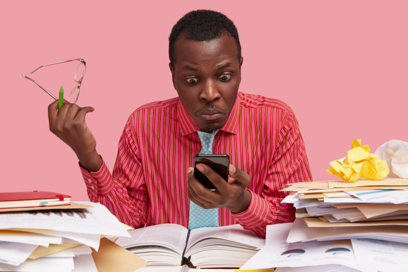 A young man is trying to research in books and on his phone to see if accepting personal checks from his employer is legal.