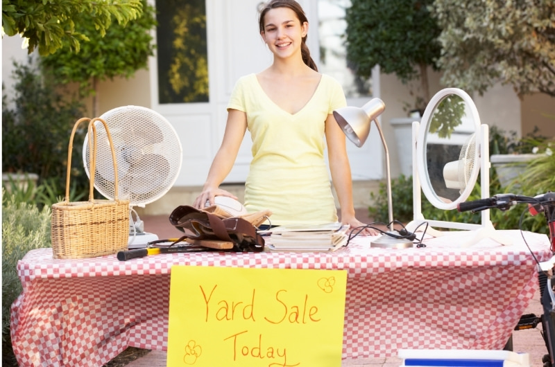 A young girl is standing behind a table with yard sale items.