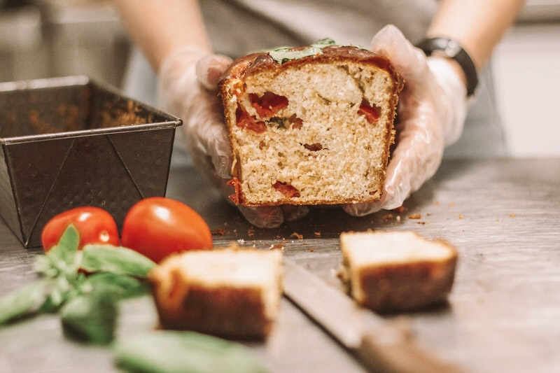 A baker is showing off a tomato basil loaf of bread that just came out of the oven. This baker makes money by shipping these loaves to customers around the country.