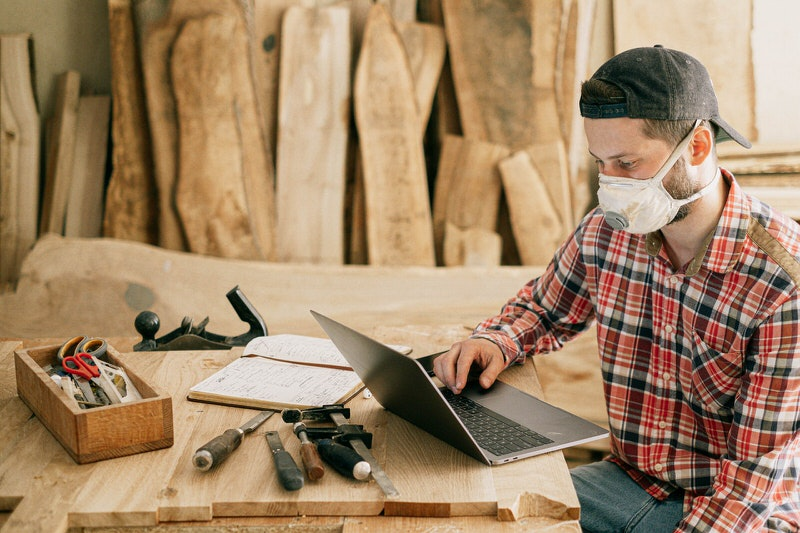 A young man who is refurbishing furniture is on his laptop looking at instructions for his latest project.