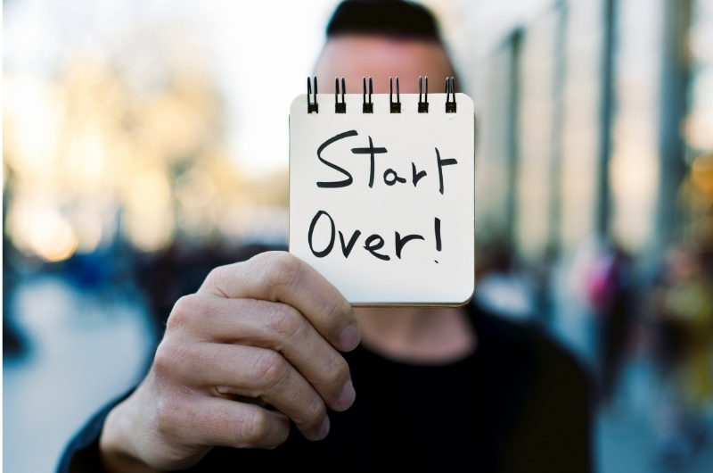 """A young man is outside and is holding out a message on a pad that says, """"start over."""""""