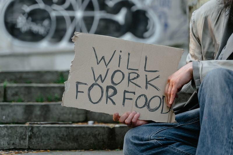 """A young man is holding a """"will work for food"""" cardboard sign to get food money while he's homeless."""