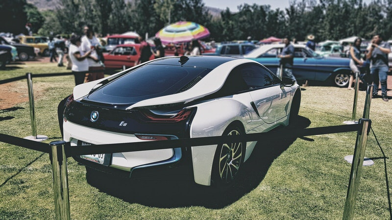 A new BMW i8 is parked at a car show for others to check out.